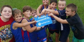 Footy boys holding the Sponsored by Hastings Co-op